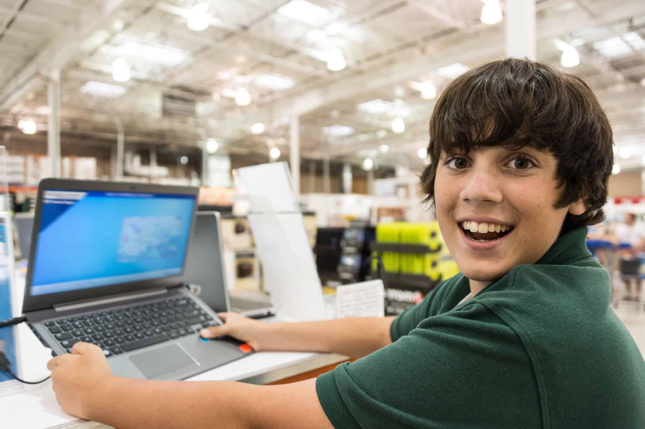 Smiling boy holding new laptop