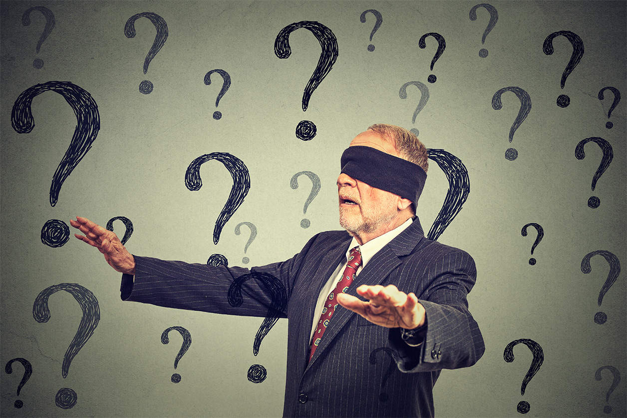Man in suit blindfolded with questions